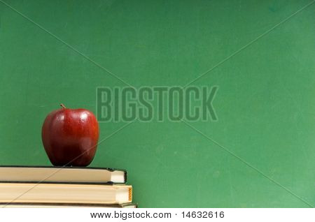 School books and apple in front of school chalkboard, blank add your own text