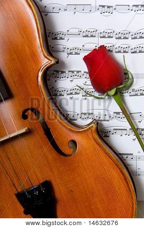 A violin, red rose and sheet music