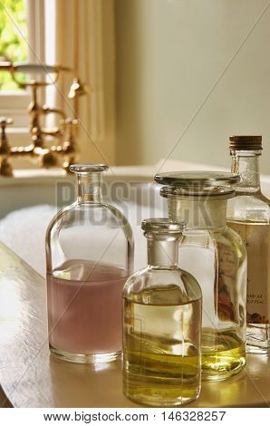 Closeup of bottles of bath oils on edge of bathtub filled with bubbles