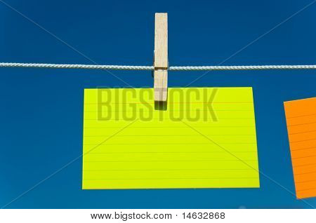 Colored notecards on a clothesline with a blue sky background