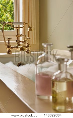 Closeup of bottles of bath oils on edge of bathtub with water running from tap