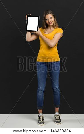 Beautiful woman in front of a black wall showing something on a tablet