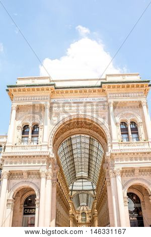 Main entrance facade of the famous Vittorio Emanuele shopping gallery in the center of Milan city.