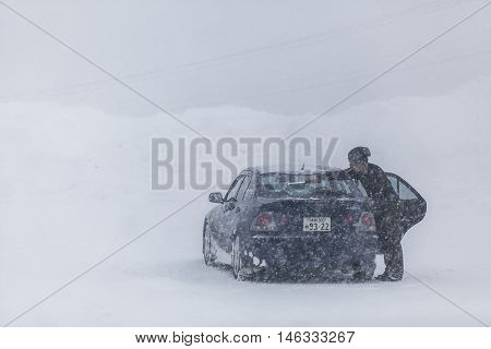 Hokkaido JAPAN - December 13 2011: The Japanese driver was sweeping snow off the windshield after the car amid a blizzard on the road at Hokkaido Japan