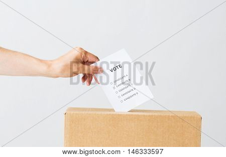 voting, civil rights and people concept - male hand putting vote into ballot box on election