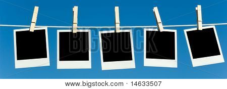 Instant transfer pictures or instant photos hanging on a clothesline with clothespins against a blue sky, includes clipping path for image area