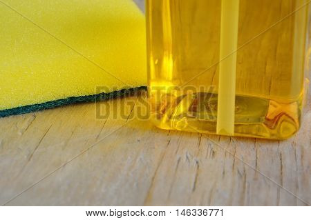 yellow dish washing soap and scrub sponge on wooden board