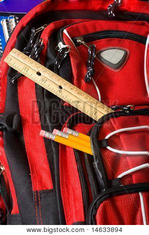 A red school backpack full of school supplies