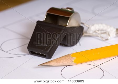 A basketball coaches items including a whistle and a clipboar with court diagrams and a pencil