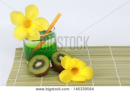 Two tone of kiwi juice served with halves kiwi and yellow flower on bamboo.