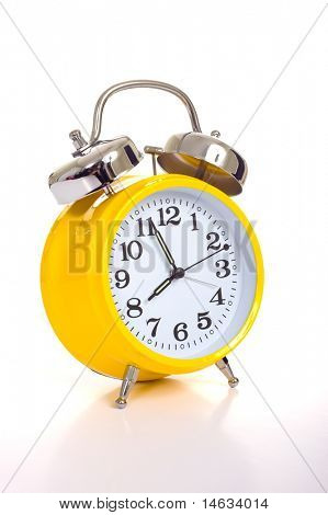 a vintage, antique yellow alarm clock on a white background