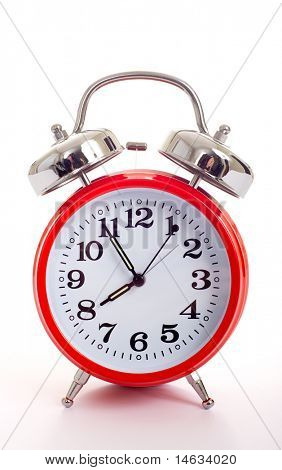 Red old fashioned alarm clock on a white background