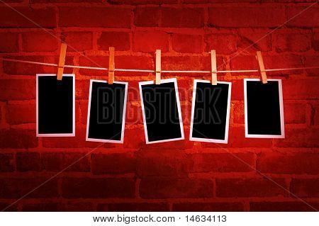 imagens ou fotografias em uma corda com prendedores de roupa, com traçado de recorte de imagens, na frente de um bri