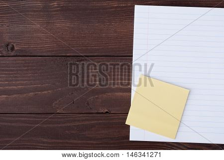 School stationery with copyspace on wooden board. Memo stick and exercise-book on wooden table