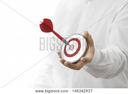 caucasian man holding a modern target with a dart in the center. image over white background. Concept of objective attainment.