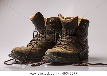 Pair of worn brown leather hiking boots with undone laces viewed low angle over a grey background
