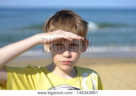 Portrait of the boy of the teenager looking afar on the seashore