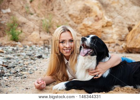 Portrait of happy blonde young woman hugging her dog on the beach
