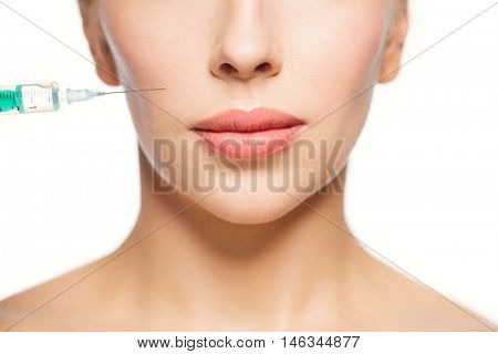 people, cosmetology, plastic surgery, anti-aging and beauty concept - beautiful young woman face and syringe making injection over white background