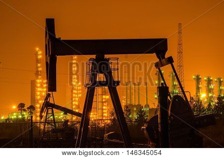 Oil rig silhouette at the background of refinery by night. Oil and gas industry.