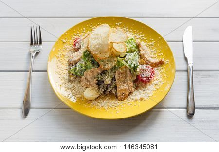 Restaurant food closeup on white wood. Beautifully decorated caesar salad with sesame, chicken, crouton and lettuce on yellow plate. Appetizing dish served with parmesan, healthy snack for dinner.