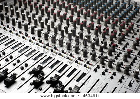 Audio recording equipment or soundboard background with many knobs and adjustments, board is a little dusty