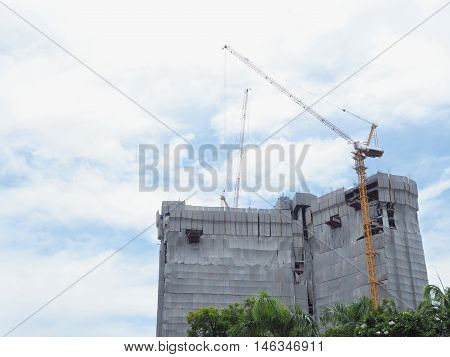 Construction site with cranes over clear blue sky background