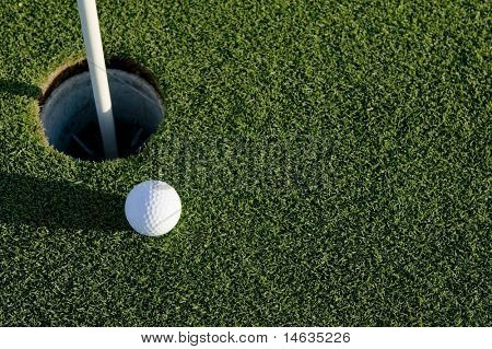 A white golf ball near the hole of a golfing green or course