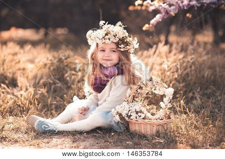 Smiling baby girl 4-5 year old wearing stylish clothes and floral hairband sitting outdoors. Childhood.