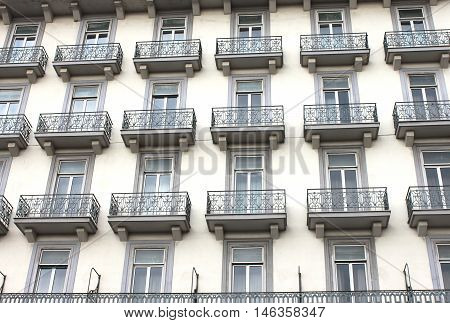 Facade of a multi-storey house with a balcony in Rome, Italy.