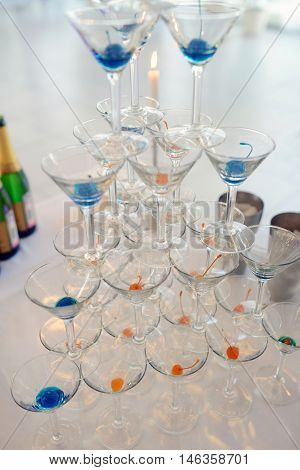 Beautiful wedding slide champagne for bride and groom indoors. Colorful glasses for alcohol with berries. Beauty of bridal interior for marriage. Bright bar for celebration