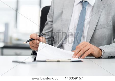 Senior analyst managing business accounts. Close up of a senior businessman hands checking final report before submission. Close up of hands of leadership signing business contract.