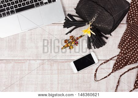 Fashion women accessories. Luxury handmade snakeskin (python) handbag, frangipani, laptop, smartphone, clothes. Top view, flat lay, light wooden  background. Free/empty space for text.