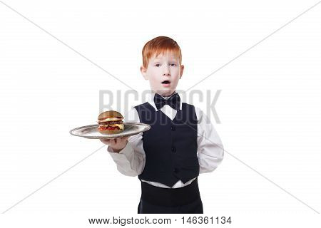 Little suprised waiter stands with tray serving hamburger. Redhead child boy in suit plays restaurant servant isolated at white background