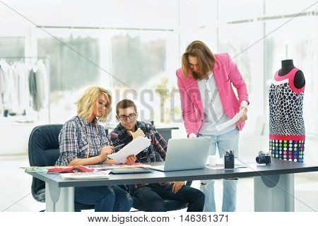 trendy designer clothes and his assistants work in the Studio
