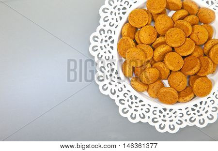Traditional Dutch candy pepernoot on white plate on grey background