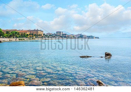 The pure waters expose the rocky seabed at the Ajaccio coast with the old town buildings on the background Corsica France.