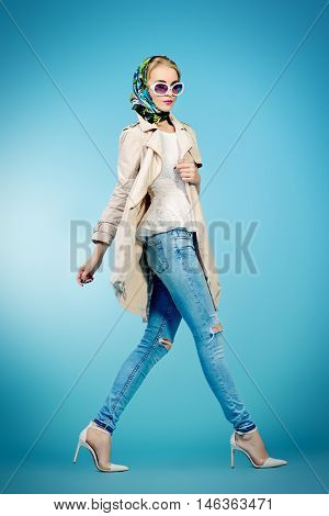 Full length portrait of an elegant young woman wearing white coat, sunglasses and headscarf posing at studio in motion. Beauty, fashion.