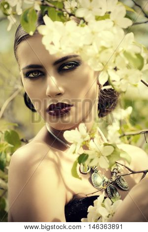 Close-up portrait of a beautiful brunette woman posing in the blossoming garden. Make-up, cosmetics. Medieval history, old times. Fashion. Gothic style.