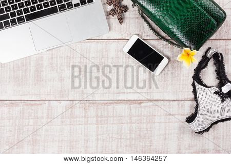 Ladies Fashion Accessories. Luxury handmade snakeskin (python) handbag, sexy panties, laptop, smartphone, frangipani flower. Top view, flat lay, light wooden  background. Free/empty space for text. Sexy meeting set.