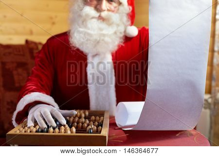 Santa Claus holding his gift list and counting