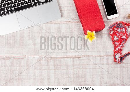 Fashion women accessories. Luxury handmade snakeskin (python) purse/wallet, laptop, smartphone, panties, frangipani flower. Top view, flat lay, light wooden  background. Free/empty space for text. Stylish set for meeting.