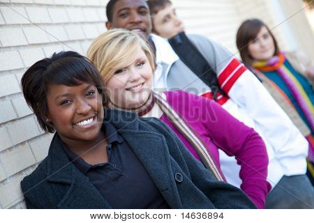 Multi-racial college students outside against a brick wall