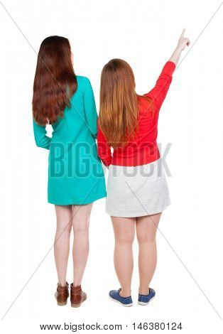 Back view of two pointing young girl. Rear view people collection.  backside view of person. beautiful woman friends  showing gesture. Rear view. Isolated over white background. Two young girls