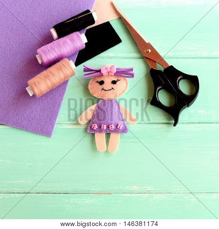 Handmade felt doll, scissors, thread, needle, flat pieces of felt on a wooden background with empty place for text. Easy sewing craft idea. Children workplace background