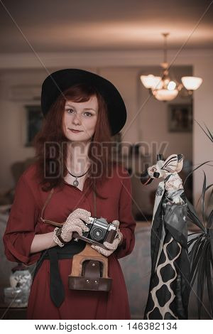 beautiful young model in a vintage costume (hat and gloves) with a old camera. photo toned vintage style