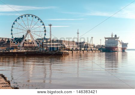HELSINKI FINLAND - MARCH 17 2015: View of the Ferris wheel the port and Viking ferry with beautiful reflection on the sea in Helsinki Finland