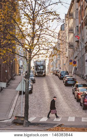HELSINKI FINLAND - OCTOBER 22 2014: Old businessman rushing across the street in a hurry in the early morning