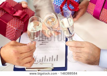 Closeup of people clinking wine glasses at christmas corporate party