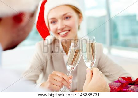 Two business colleagues clinking champagne glasses in office